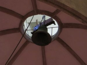 A bell being lowered through the roof of the nave